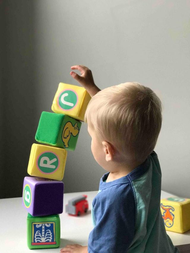 Baby der leger med legetøj